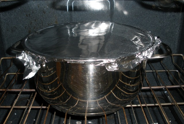 I covered it with foil because my Dutch oven has a glass lid with a gasket.  I don't trust that gasket in the oven.