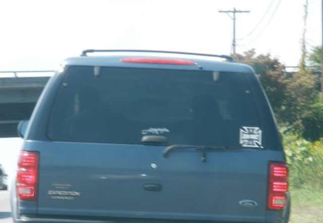 "This is blurry a little, so let me narrate.  That cross over on the right side says ""Jesus Christ.""  That thing in the middle is a decal of a machine gun.  WWJD?"