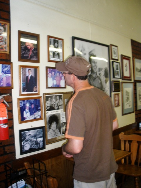 "The Beloved checking out Snappy Lunch's Wall o' Fame.  We didn't recognize anyone except Donna Fargo.  She sang ""The Happiest Girl in the Whole USA."""